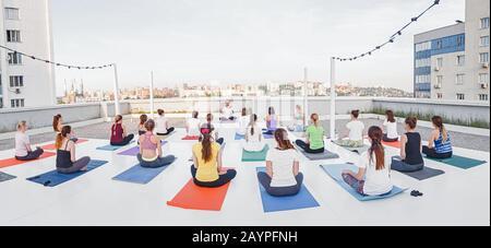 01 JUILLET 2018, UFA, RUSSIE: Un groupe de personnes dans poses asana faire des exercices de yoga sur le toit Banque D'Images
