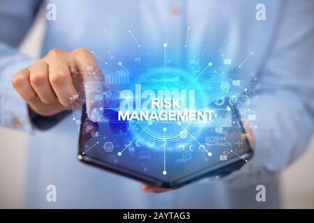 Businessman holding a smartphone pliable avec la GESTION DES RISQUES DE L'inscription, nouveau concept commercial