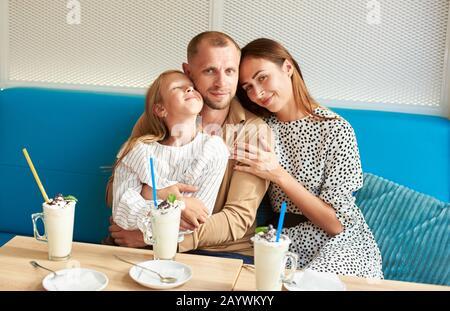 Le père affectueux embrasse sa fille alors que sa femme l'embrasse, souriant et regardant dans l'appareil photo, assis dans le café sur un canapé bleu, milkshakes sur la table Banque D'Images
