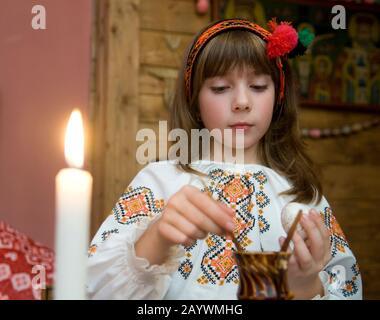 Kolomyia, Oblast D'Ivano-Frankivsk/Ukraine - 10.07.2008. Fille vêtue de costumes folkloriques ukrainiens peint des œufs pour Pâques. Banque D'Images