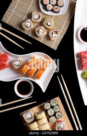 Sushi avec baguettes. Les sushis roulent la cuisine japonaise au restaurant. Jeu de rouleaux de sushi de Californie avec saumon, légumes. Image verticale