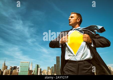 Un jeune homme d'affaires fort révélant son super-héros intérieur au-dessus de la ville dans un ciel bleu clair et ensoleillé Banque D'Images
