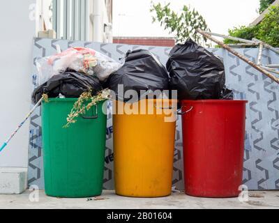 Bacs verts, jaunes et rouges remplis de déchets Banque D'Images