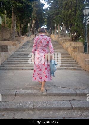 Femme dans une robe rouge marchant dans l'escalier sur la colline de Calvary dans la ville espagnole d'Arta sur l'île méditerranéenne de Majorque (Majorque) Banque D'Images