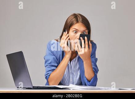 Une femme en colère dans un t-shirt blanc hurlant au téléphone, regardant à l'écran, ennuie femme lire de mauvaises nouvelles, problème avec téléphone portable cassé ou déchargé, Banque D'Images