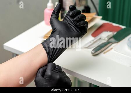 Gants médicaux en latex noir à la main du cosmologiste, gros plan. Banque D'Images