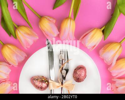 Beau luxe table de pâques couverts en couteau, fourchette avec tulipes colorées et des œufs peints en or avec un brillant sur la surface rose. Fond de vacances, carte de vœux, gros plan
