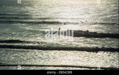 Un surfeur fait une vague tandis que d'autres surfeurs attendent, Fistral Beach, Newquay, La Cornouaille Coast, Angleterre