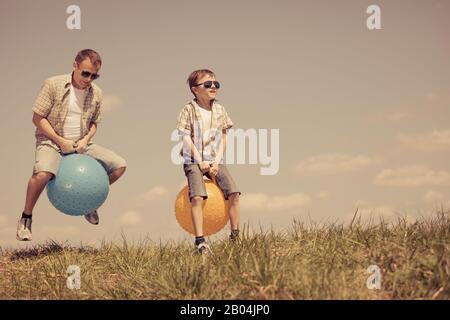 Père et fils jouant sur le terrain à la journée. Les gens s'amuser à l'extérieur. Ils sauter sur des ballons gonflables sur la pelouse. Concept de friendly fam Banque D'Images