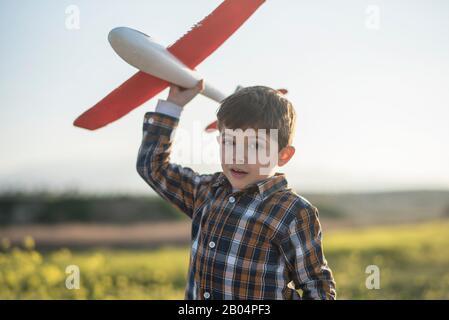 Petit garçon avec un avion jouet jouant au printemps extérieur image Banque D'Images