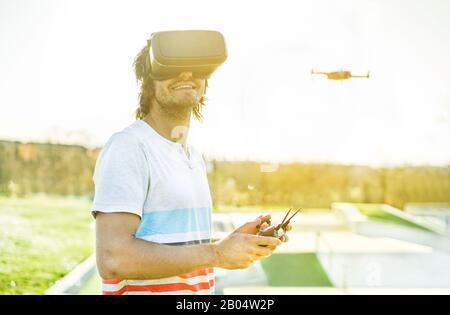 Jeune homme utilisant un drone avec télécommande portant des lunettes de réalité virtuelle faisant des photos et des vidéos - jeune gars s'amuser avec la nouvelle technologie tre Banque D'Images