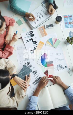 Gros plan de l'équipe de concepteurs assis à la table et travaillant avec des croquis de mode de vêtements en équipe à la réunion Banque D'Images