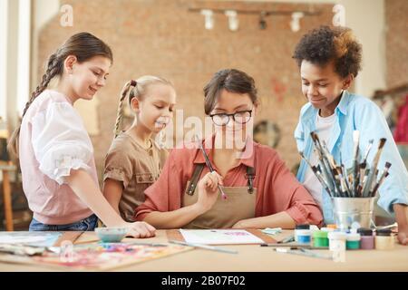 Jeune professeur de lunettes assis à la table et montrant comment dessiner une photo à ses élèves au studio d'art Banque D'Images