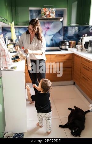 Valeurs familiales: Mère et père jouant avec bébé enfant garçon intérieur - Parents portant des vêtements de maison bleu et gris et leur fils noir et blanc - Heureux Banque D'Images