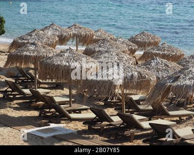 Chaises longues en bois désertes avec parasols en paille sur une plage de sable à Evia, Grèce. Mer bleue derrière. Banque D'Images