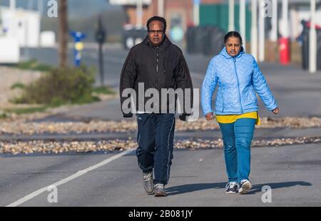 Asiatique (peut-être indien) couple de personnes marchant ensemble le long d'une promenade en Angleterre, Royaume-Uni, portant des manteaux sur une journée froide.