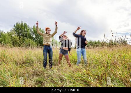 Vacances d'été vacances concept de personnes heureuses. Groupe de trois amis garçon et deux filles sauter, danser et s'amuser ensemble à l'extérieur. Pique-niquez avec des amis lors d'un voyage sur route dans la nature Banque D'Images