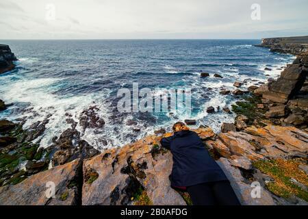 Vue panoramique d'une femme située sur une falaise surplombant l'océan