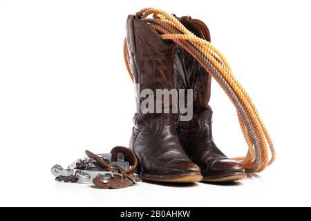 Bottes occidentales et une corde de tour ou de lariat et des espions sur un fond blanc