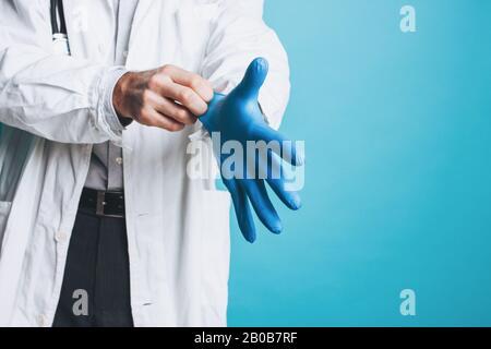 La photo de récolte de l'homme médecin en manteau blanc met sur des gants médicaux en caoutchouc isolés sur le fond bleu Banque D'Images
