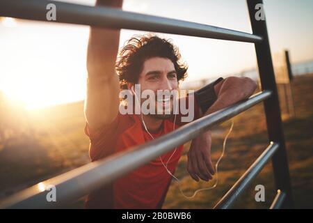 Portrait d'un jeune coureur masculin joyeux avec des écouteurs dans ses oreilles penchant sur la rampe après s'être fait dans le parc un jour ensoleillé