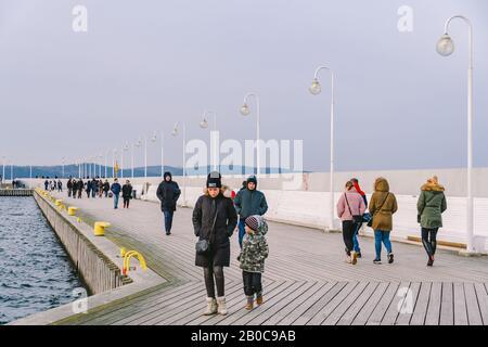 Une foule de personnes marche sur un quai en bois à Sopot, en Pologne, le 20 juillet 2020, lors d'une journée d'hiver ensoleillée près de la mer Baltique. Vacances d'hiver près de Banque D'Images