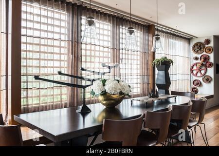 Luminaires suspendus en verre au-dessus de la table à manger De L'Arxe avec hydracea dans un vase en cuivre