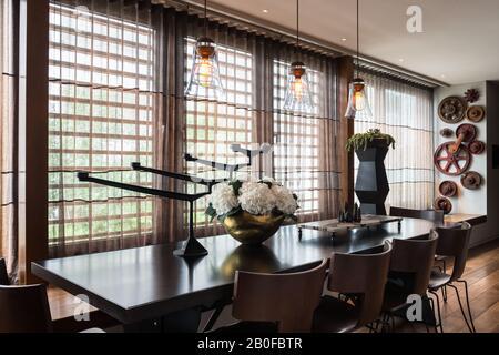 Luminaires suspendus en verre au-dessus de la table à manger avec hydracea dans un vase en cuivre