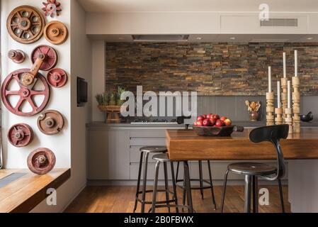 Bar à petit-déjeuner en teck avec murs ornés d'ardoise dans la cuisine de l'appartement moderne de West London.
