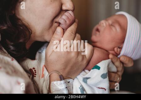 Gros plan de la mère à l'hôpital embrassant la main du nouveau-né