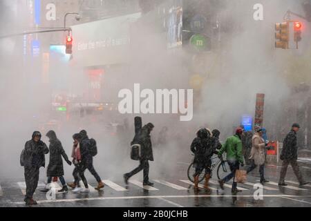 La vapeur monte et dévie au-dessus de l'Avenue parmi les bâtiments de Midtown Manhattan lors de la journée de neige autour De Times Square à New York City NY USA en janvier 2020. Banque D'Images