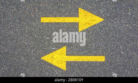 Deux flèches jaunes sur l'asphalte. Concept, directions radicalement différentes. Banque D'Images