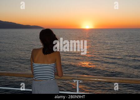 Un adolescent asiatique en métro se tenant sur la terrasse du ferry en regardant le coucher du soleil sur le ferry à destination de Lesvos Banque D'Images