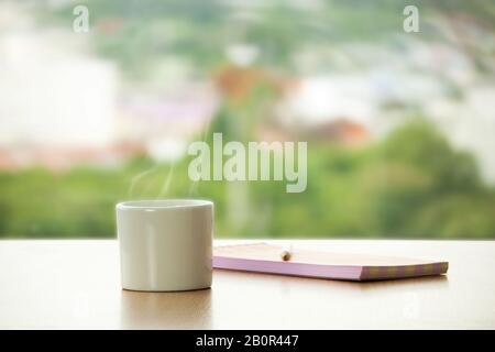 tasse de café chaud avec crayon et livre de notes sur la table dans le café. café vue fenêtre avec arbre vert pour se sentir frais comme arrière-plan. créatif et idée Banque D'Images