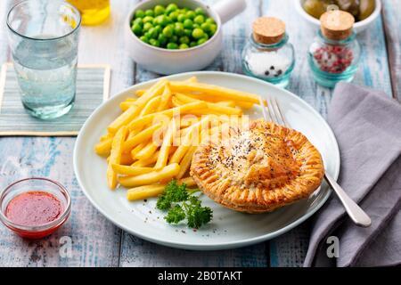 Tarte à la viande avec frites sur une plaque blanche. Fond en bois. Gros plan. Banque D'Images