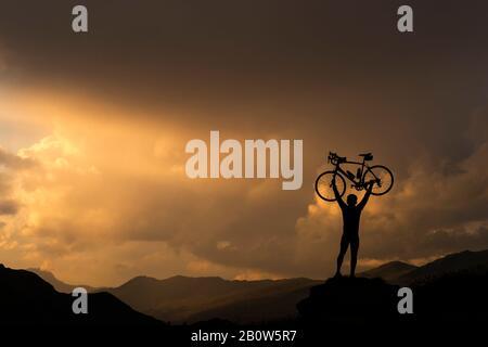 Cycliste levant la bicyclette contre le coucher du soleil sur la colline Banque D'Images