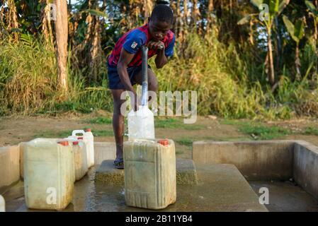 Garçon fetche l'eau d'un puits, forêt équatoriale, Gabon, Afrique centrale