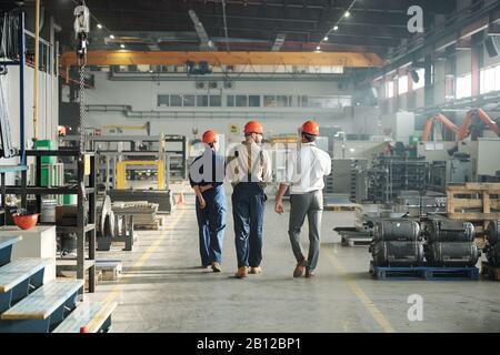 Vue arrière de trois travailleurs d'une usine industrielle marchant le long d'une grande usine Banque D'Images