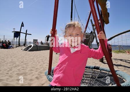 Petite fille blonde de 6 ans sur une aire de jeux à Westerland, Ile de Sylt, Allemagne, Europe Banque D'Images