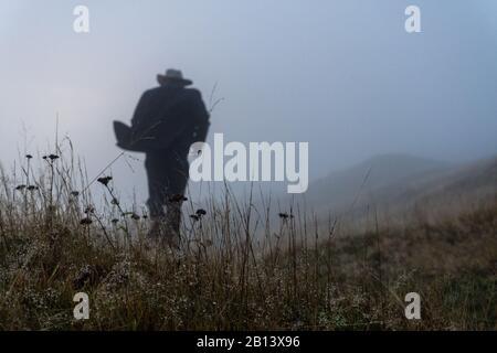 concept de noir de film. Un homme flou et hors de la mise au point avec un long manteau et un chapeau qui s'éloigne de l'appareil photo. Silhouetted dans la brume. Banque D'Images