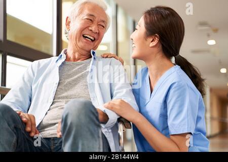 une jeune femme asiatique sympathique discutant avec un homme senior heureux dans le couloir de la maison de soins infirmiers Banque D'Images