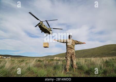 Le sergent de l'armée américaine. Keith Beardsley, un instructeur d'assaut aérien avec le guerrier fantôme Academy, les signaux d'un hélicoptère CH-47 Chinook à planer pendant une charge au centre de formation de Yakima, Yakima, Washington, 5 mai 2017. Les opérations de charge de l'élingue unités permettent d'accomplir leur mission en déplacement rapide des fournitures et de l'équipement, en contournant les obstacles de surface. (U.S. Photo de l'armée par le Sgt. Kalie Jones) Banque D'Images