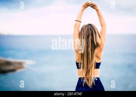 Mode de vie sain concept de personnes avec belle fille blonde de cheveux belle vue de l'arrière faire quelques étirements devant l'océan vue extérieur - la coupe wom
