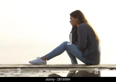 Vue latérale portrait d'une fille triste regardant loin seul assis dehors contemplant horizon