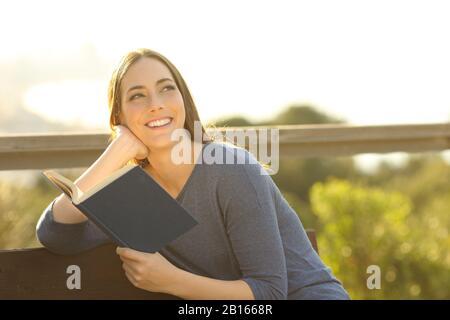 Une heureuse femme tenant un livre de papier pensant regarder le côté au coucher du soleil dans un parc Banque D'Images