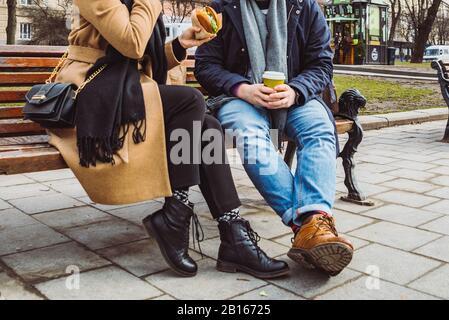 Droit de récolte. couple sitting on bench eating fast food boire le thé Banque D'Images