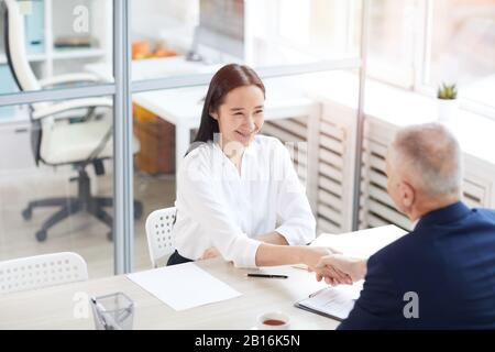 Portrait en grand angle de la jeune femme d'affaires asiatique souriant avec plaisir tout en secouant les mains avec un homme d'affaires à travers la table au bureau, espace de copie