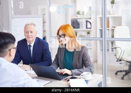 Portrait de deux responsables RH interviewant un jeune homme asiatique pour un poste au bureau, espace de copie Banque D'Images