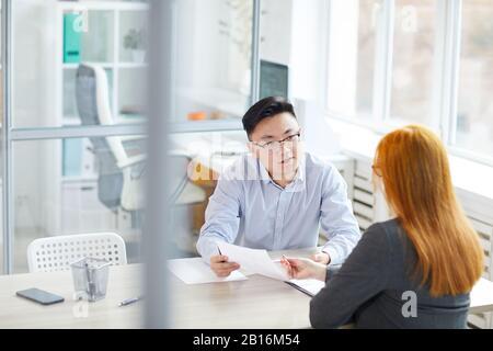 Portrait de jeune homme d'affaires asiatique interviewer une jeune femme pour un poste dans un bureau moderne, espace de copie