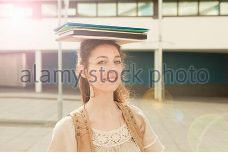 Young woman balancing books on head Banque D'Images